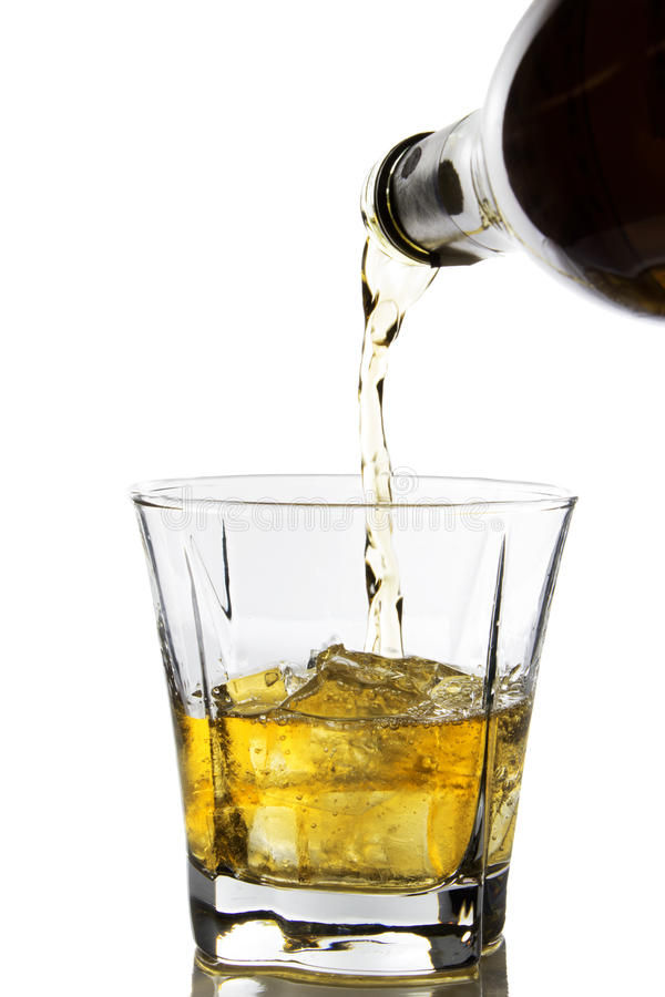 Whiskey. Double whiskey being poured into a glass against white background royalty free stock photos