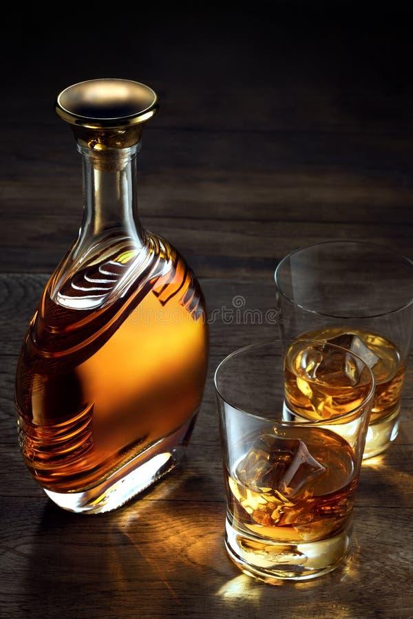 whiskey e una bottiglia da parte sul fondo di legno di colore fotografia stock libera da diritti