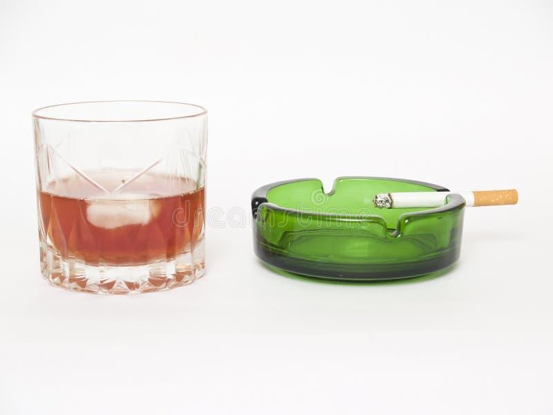 whiskey för askfatcigarettexponeringsglas arkivbild