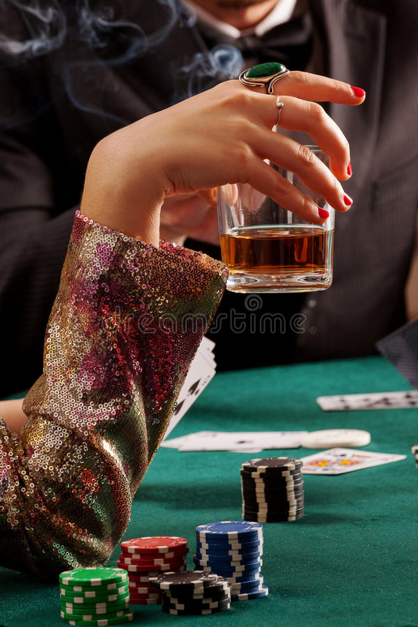 Whiskey and gambling. A closeup of a women drinking a glass of whiskey while gambling stock image