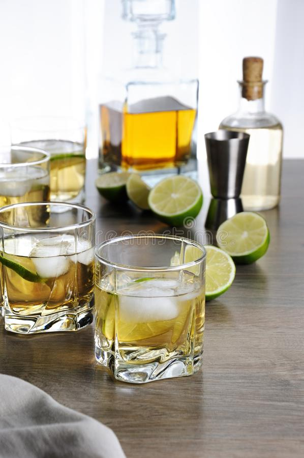 Whiskey with ginger ale and lime. Alcohol cocktail with brandy, whiskey or rum with Ginger Ale, lime and ice in glasses royalty free stock photos