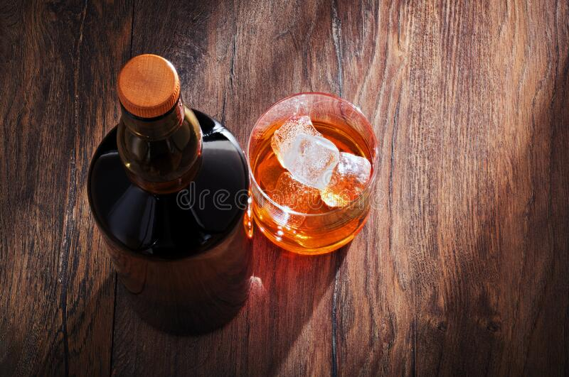 Whiskey glass with bottle and ice on wooden bar table stock photos