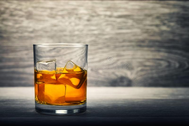 Whiskey glass and ice on wooden background stock photos