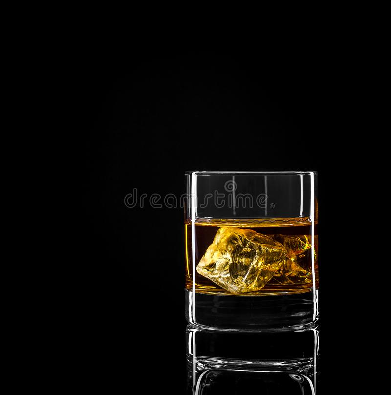 Whiskey glass with golden alcohol and ice cube stock photo