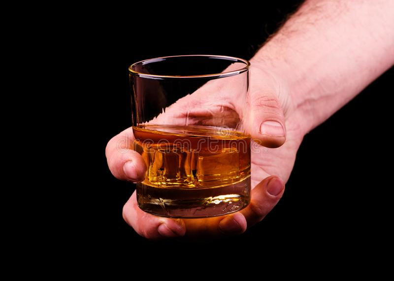 Whiskey glass in a hand of a man on black background, brandy in a glass royalty free stock photo