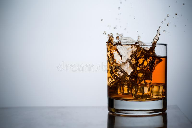 Whiskey in a glass with ice. Spray and drops. Concept with a drink. Copy space. Close up and horizontal orientation stock photo