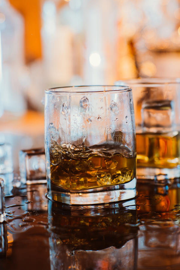 Whiskey glass with ice and warm light on black table with reflection, warm atmosphere royalty free stock images
