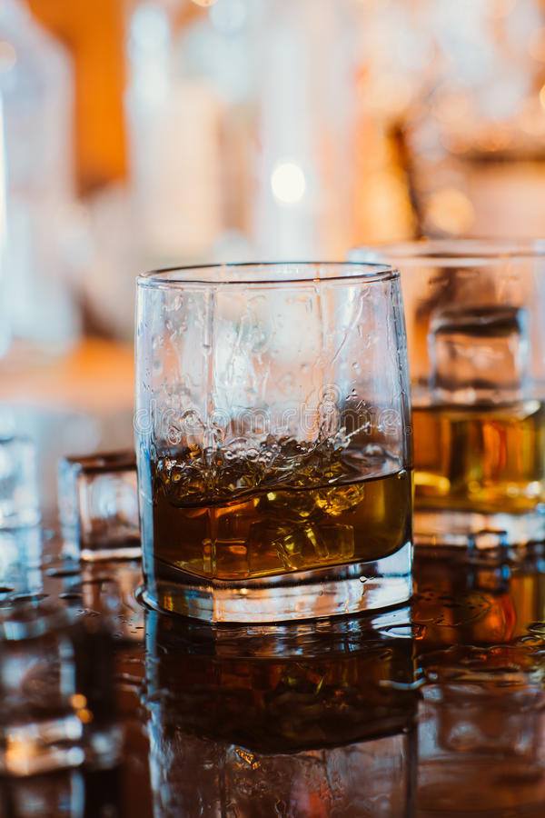 Whiskey glass with ice and warm light on black table with reflection, warm atmosphere royalty free stock photography