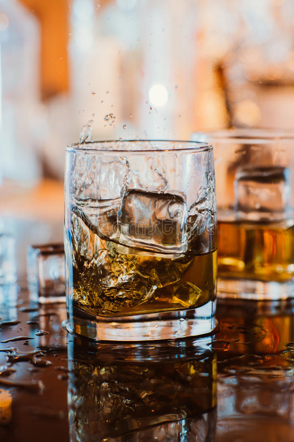 Whiskey glass with ice and warm light on black table with reflection, warm atmosphere royalty free stock photo