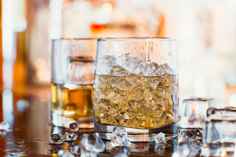 Whiskey glass with ice and warm light on black table with reflection, warm atmosphere stock image