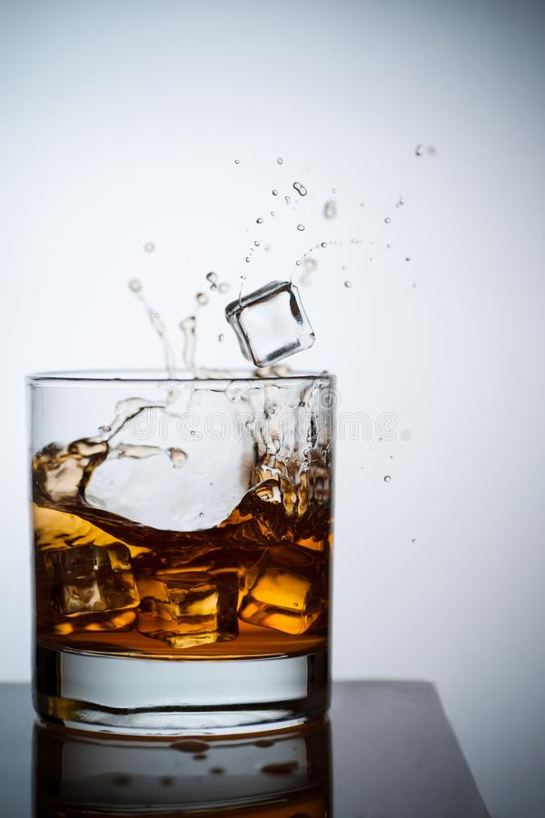 Whiskey in a glass with ice. Spray and drops. Concept with a drink. Copy space. Close up and vertical orientation royalty free stock photography