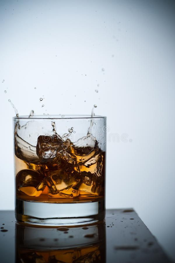 Whiskey in a glass with ice. Spray and drops. Concept with a drink. Copy space. Close up and vertical orientation stock image