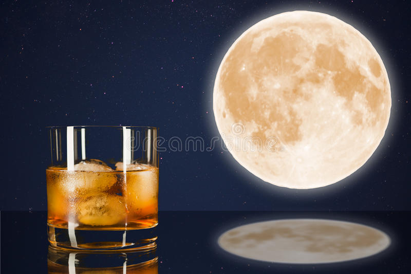Whiskey glass on midnight sky with full moon background. stock photo