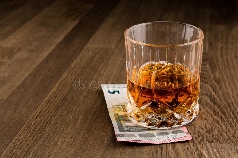 Whiskey Glass over Euro banknotes isolated on Wooden Table. royalty free stock photo