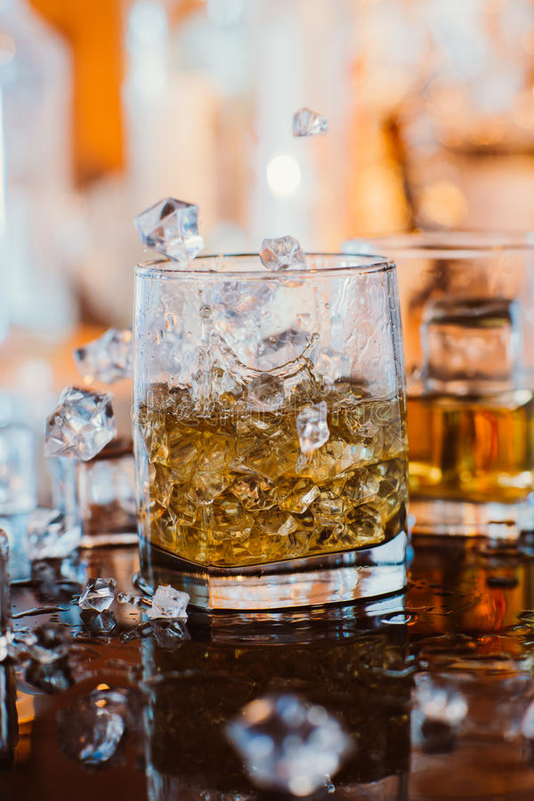 Free Whiskey Glass With Ice And Warm Light On Black Table With Reflection, Warm Atmosphere Stock Photos - 51664823