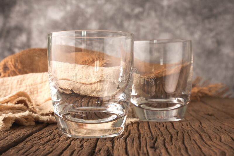 A whiskey glass on a wooden table royalty free stock photography