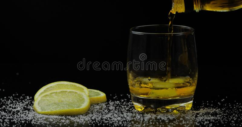 Whiskey with ice. Pouring whisky rum from the bottle on black background. Whiskey with ice. Adding ice cubes and pouring whisky from the bottle on black royalty free stock images