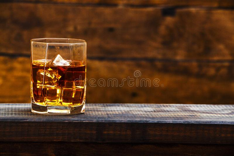 Whiskey with ice or brandy in a glass and a square carafe on an old wooden background. Whiskey with ice in a glass. Whiskey or cog stock photo