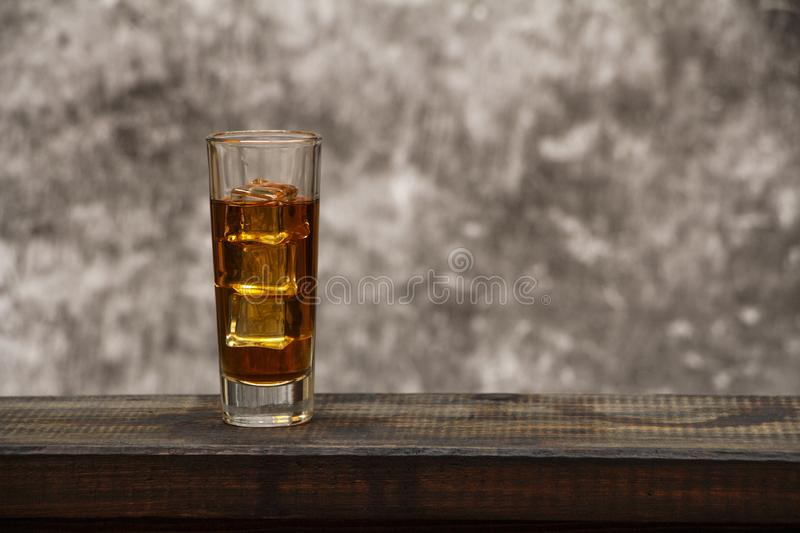 Whiskey with ice or brandy in a glass and a square carafe on an old wooden background. Whiskey with ice in a glass. Whiskey or cog royalty free stock photo