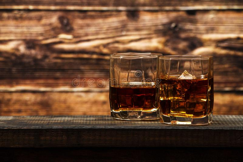 Whiskey with ice or brandy in a glass and a square carafe on an old wooden background. Whiskey with ice in a glass. Whiskey or cog stock photos