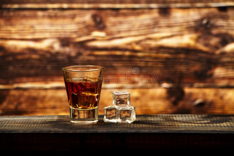 Whiskey with ice or brandy in a glass and a square carafe on an old wooden background. Whiskey with ice in a glass. Whiskey or cog stock image