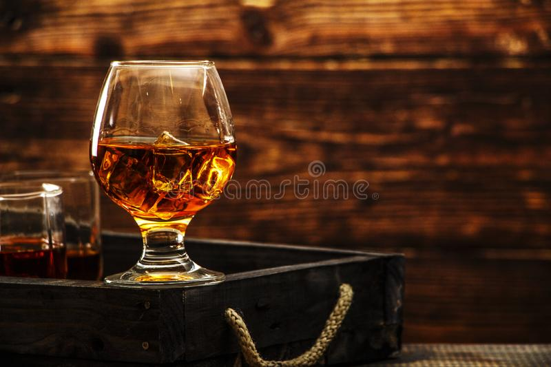 Whiskey with ice or brandy in a glass and a square carafe on an old wooden background. Whiskey with ice in a glass. Whiskey or cog stock photography