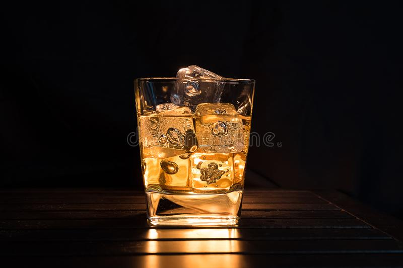 Whiskey with ice cubes in glass on dark background and wood table, relax with whisky concept on the warm atmosphere stock photos