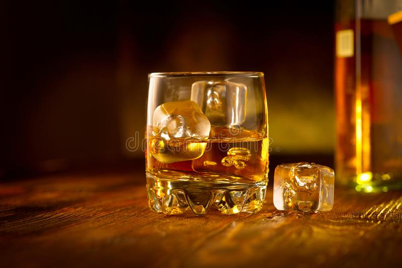 Whiskey with ice cubes. Glass of Whisky and the bottle on wooden table over dark background. Glass of rum alcohol close-up. Cognac closeup, Spirits drink royalty free stock images