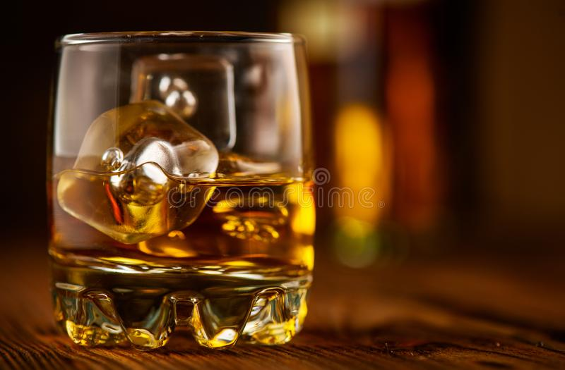 Whiskey with ice cubes. Glass of Whisky and the bottle on wooden table over dark background. Glass of rum alcohol close-up stock photography