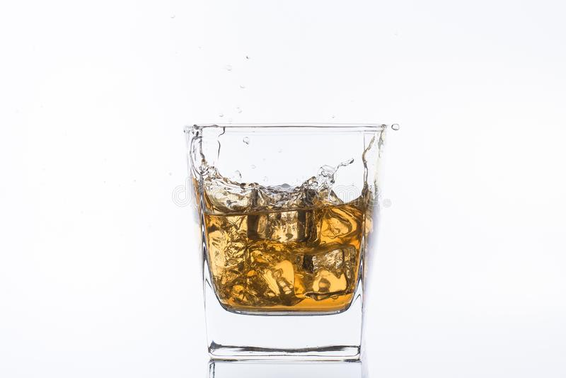 Whiskey with ice. Rum with ice. Brown brandy with ice. Three ice cubes in a glass with alcohol. stock photos