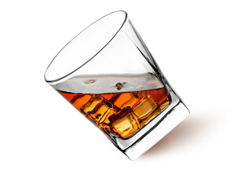 Whiskey with ice in a tilted glass royalty free stock image