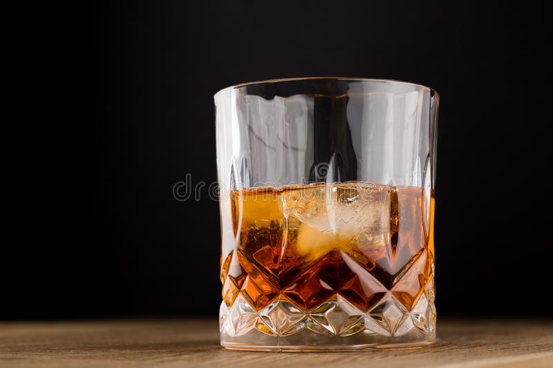 Whiskey with Ice on Wooden Table and black background. stock images