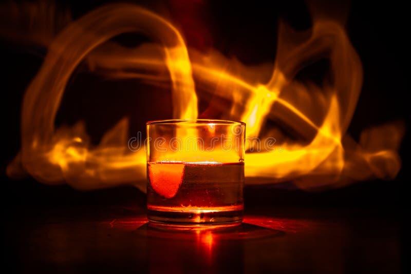 Whiskey nel concetto del fuoco Vetro di whiskey e di ghiaccio su superficie di legno con la luce e la nebbia di colore su fondo F fotografia stock