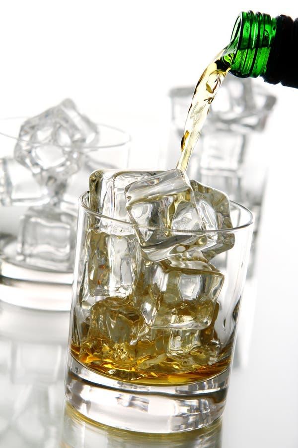 Whiskey pleuvant à torrents dans la glace images libres de droits