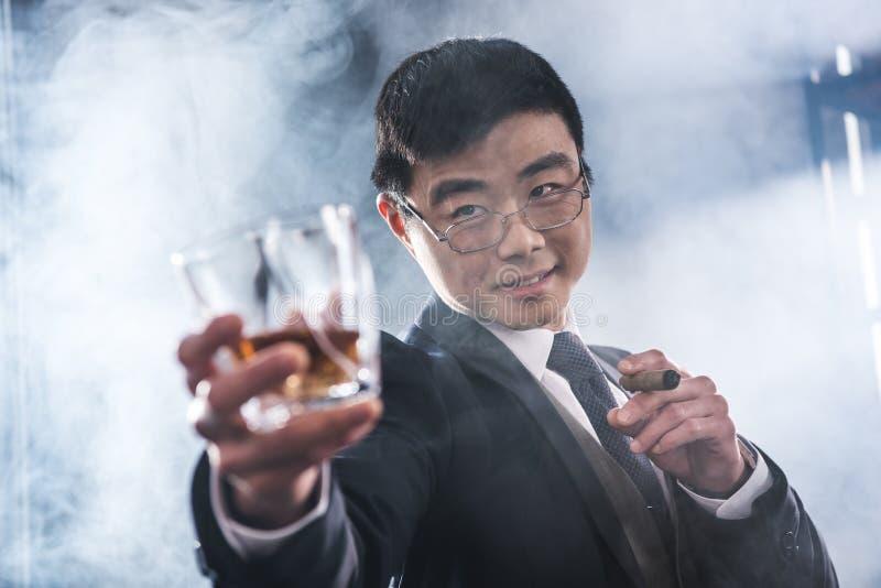 Whiskey potable d'homme d'affaires asiatique sûr et cigare de tabagisme photo stock