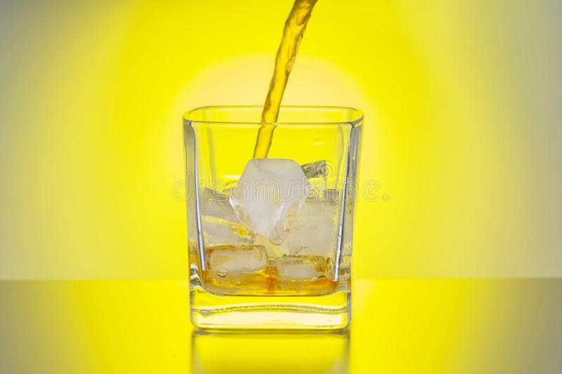 Whiskey is poured into a transparent glass with ice against the background of a yellow light source. Whiskey is poured into a transparent glass with ice against stock photography