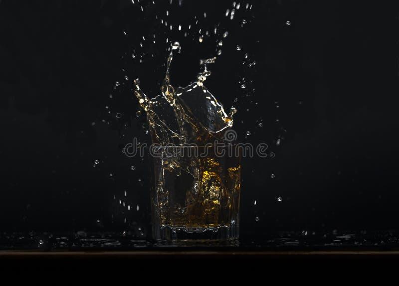 Whiskey pronto con i cubetti di ghiaccio che cadono nel vetro, spruzzanti il liquido fotografie stock libere da diritti