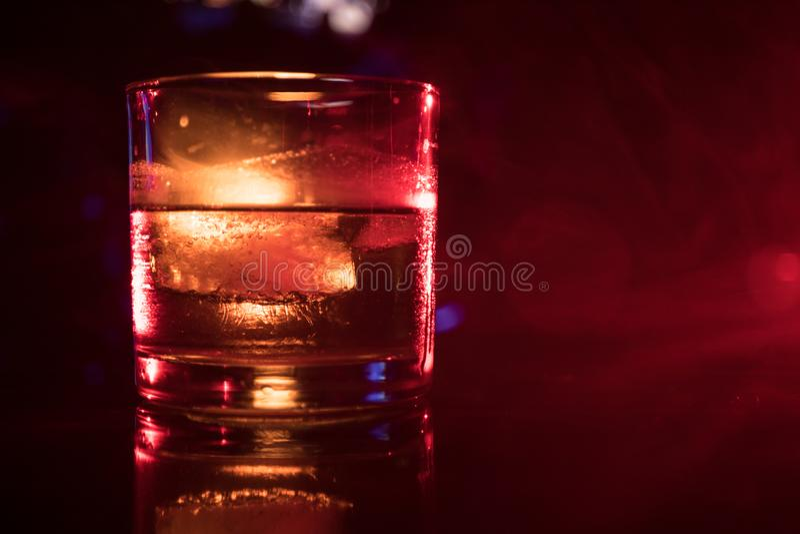 whiskey puro del fuoco selettivo con il cubetto di ghiaccio dentro il vetro del whiskey sul concetto nebbioso scuro della bevanda immagine stock libera da diritti