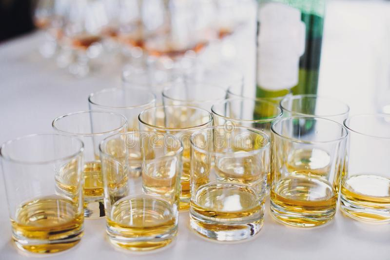 Whiskey row on table party at wedding reception. Whisky in glasses at alcohol bar. Christmas and New Year feast. Celebrations and stock image
