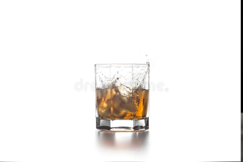 Whiskey splash from the fallen ice cube into glass with beverage on light background stock image