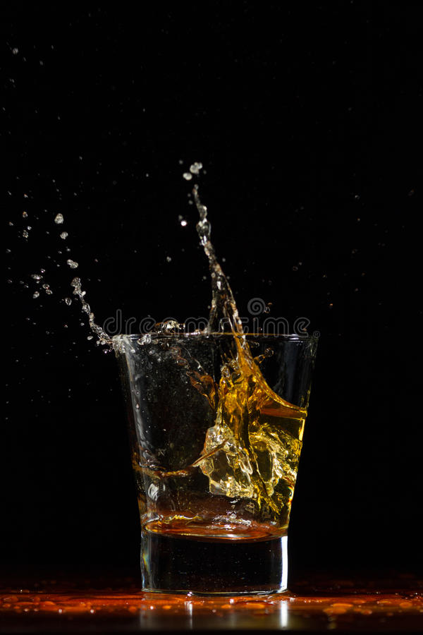 Whiskey splash in glass on black. Whiskey glass on black wood surface stock image