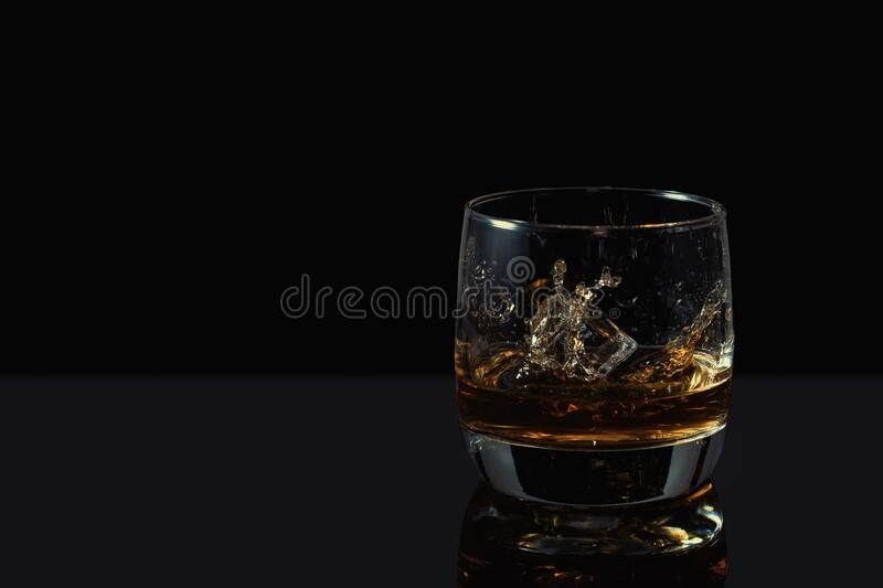Whiskey splash in glass with ice on a dark background.  stock photos