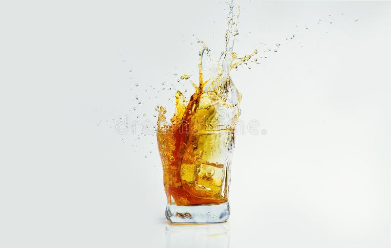 Whiskey with splash on white background, brandy in a glass stock photo