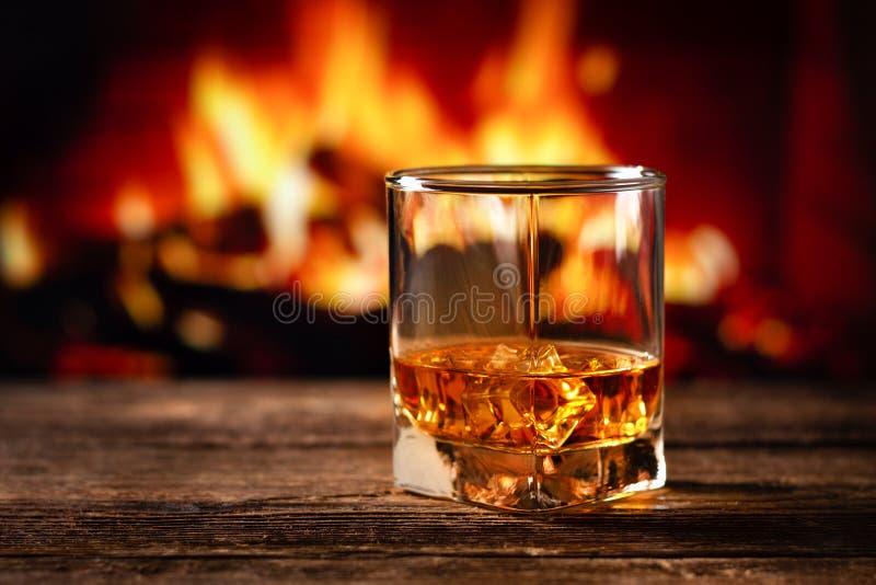 Whiskey in un vetro con fuoco nel camino sui precedenti immagine stock