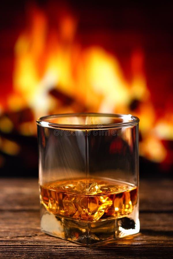 Whiskey in un vetro con fuoco nel camino sui precedenti immagini stock libere da diritti