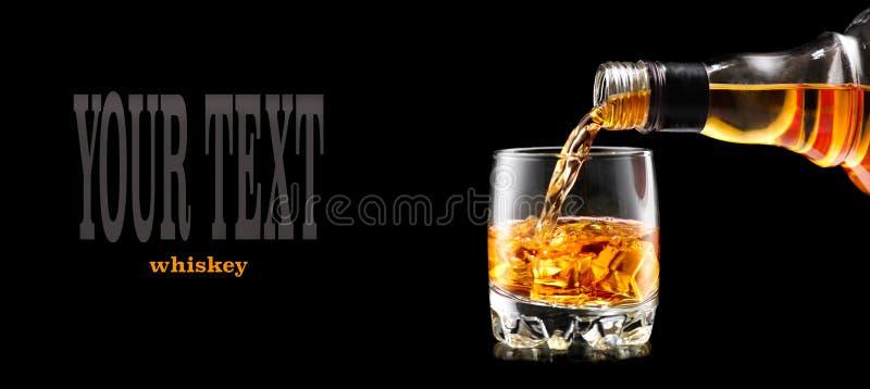 Whiskey versant de la bouteille au-dessus du noir Whiskey sur les roches image stock