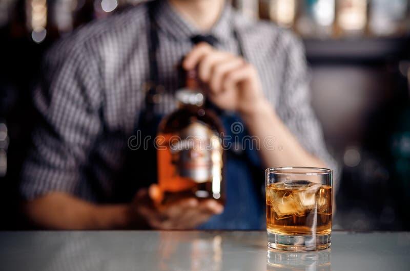 Whisky alkoholu szkło z lodem na barze, w tło barmanu chwytów butelce Ciemny cie? obrazy stock
