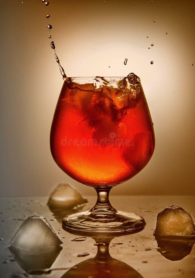 Whisky, borbón, brandy o coñac con hielo en un fondo anaranjado fotos de archivo