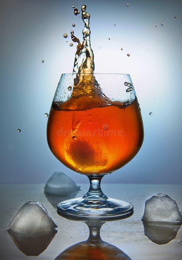 Whisky, bourbon, brandy lub koniak z lodem na błękitnym tle, fotografia stock