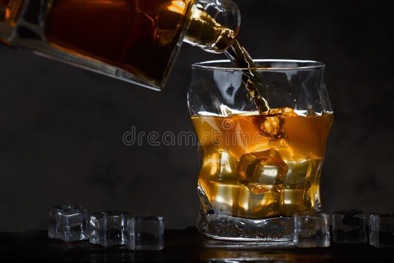 Whisky butelki spływanie w szkło fotografia stock